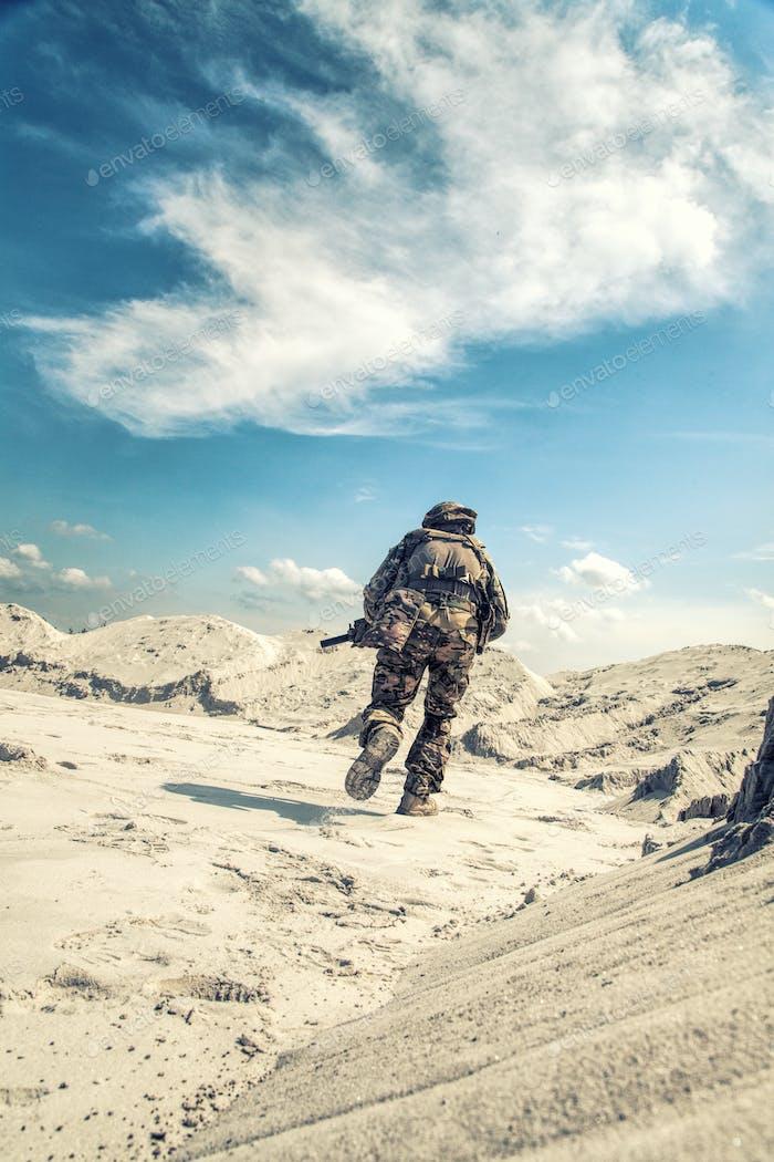 Mann in Militäruniform spielen Airsoft im Sand