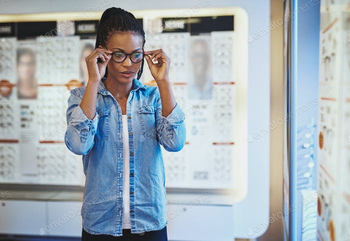 Young adult female testing the fit for eyeglasses