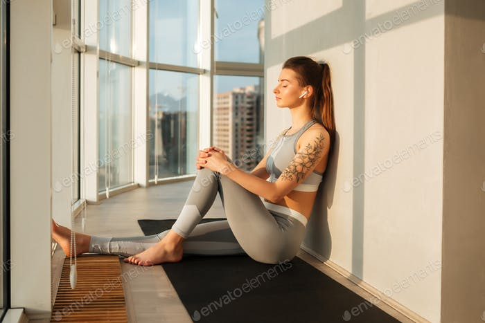 Thoughtful lady in sporty top and leggings listening music in earphones over beautiful window