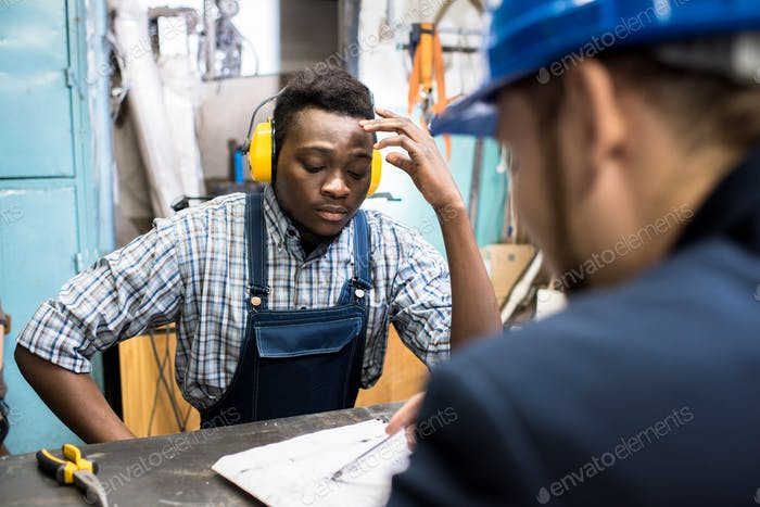 Concentrated manual worker listening to plan of boss