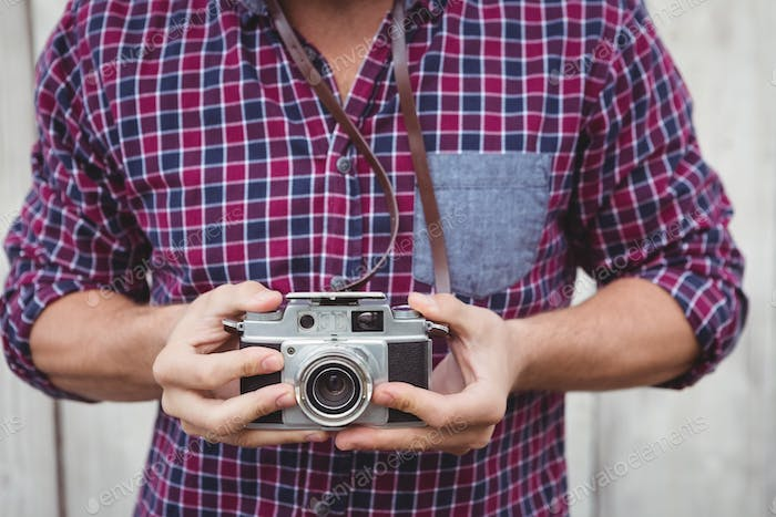 Mid section of man using camera against wooden wall