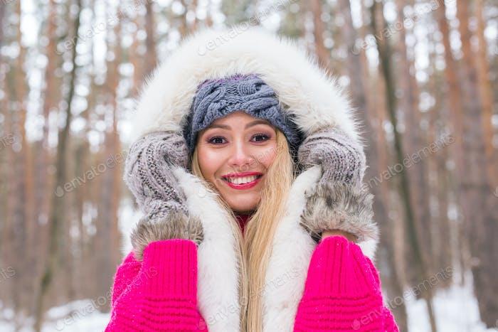 Mode, Winter und Menschen Konzept - Junge attraktive Frau in Pelzweste über verschneite gekleidet