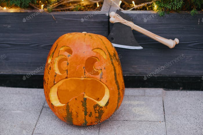 Carved pumpkin with scary face and ax