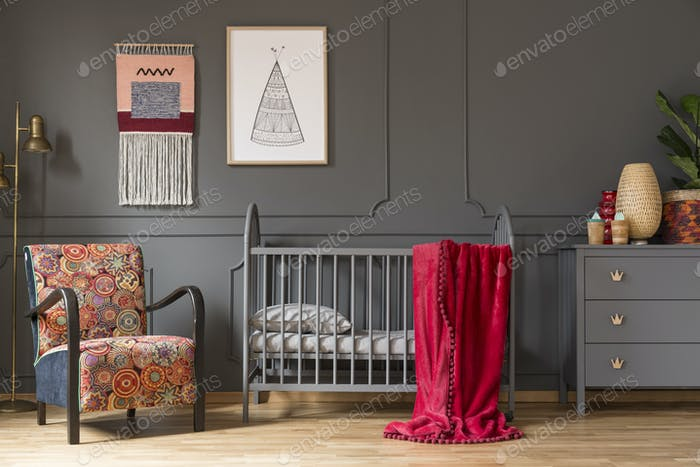 Real photo of a baby crib with a red blanket, an armchair, lamp