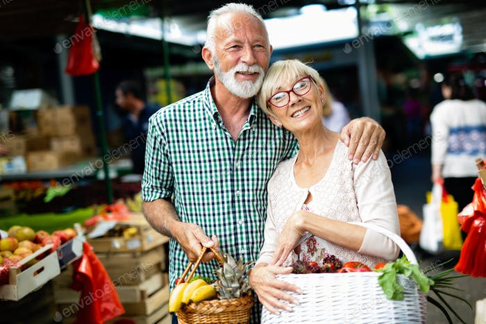 Beautiful senior couple choosing health products in the market