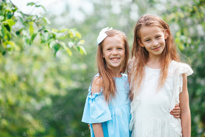 Adorable little girls in blooming apple tree garden on spring day