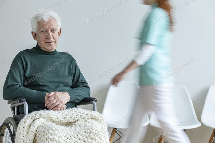 Sad paralyzed elderly man in the wheelchair in the nursing house