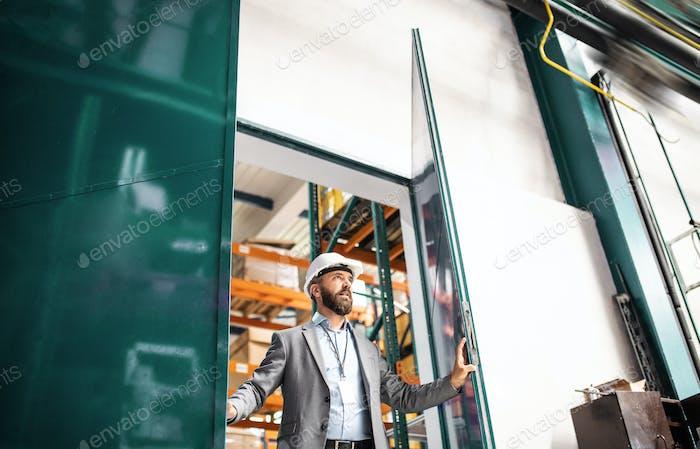 Ein Industriemann Ingenieur in einer Fabrik, der das Tor öffnet.