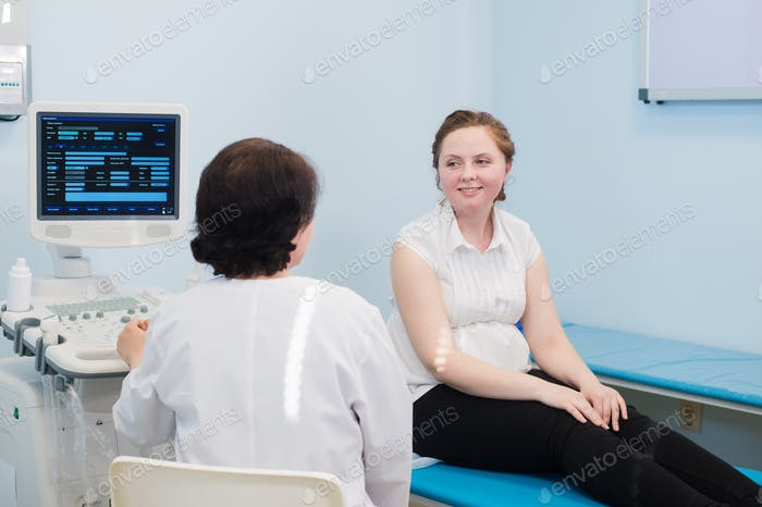 Satisfied pregnant woman having doctor's appointment with ultrasound diagnostics