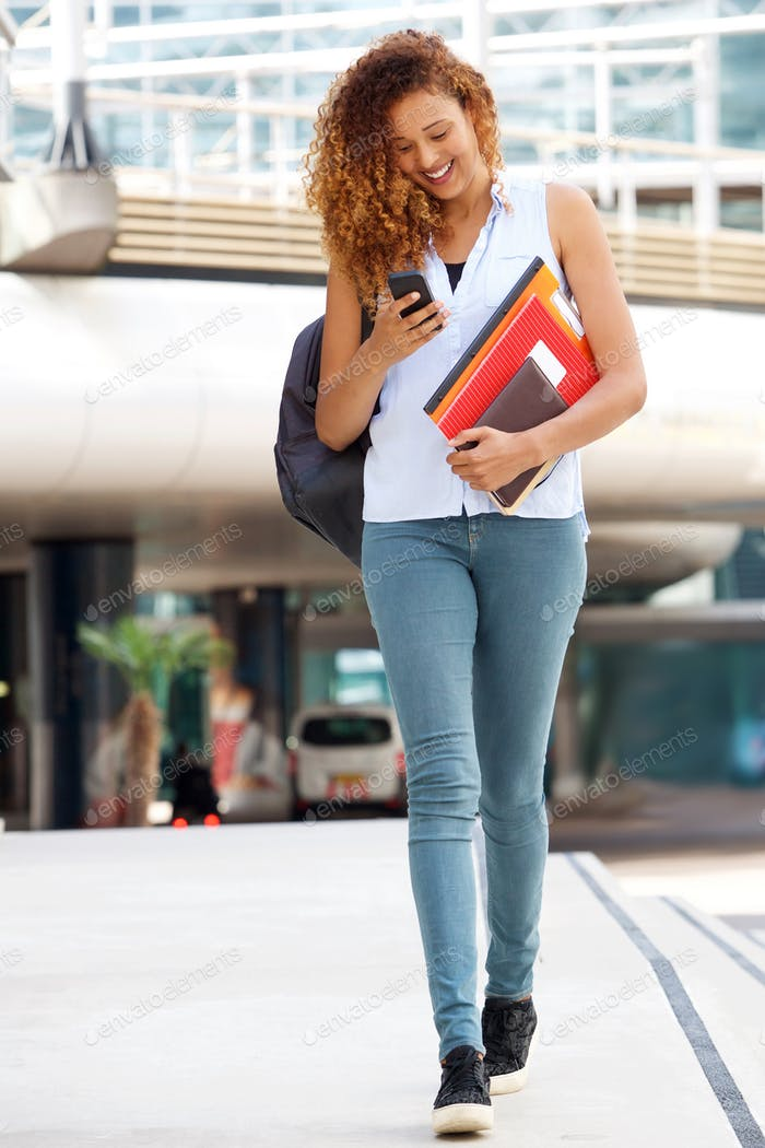 Full body happy female student walking outside with cellphone