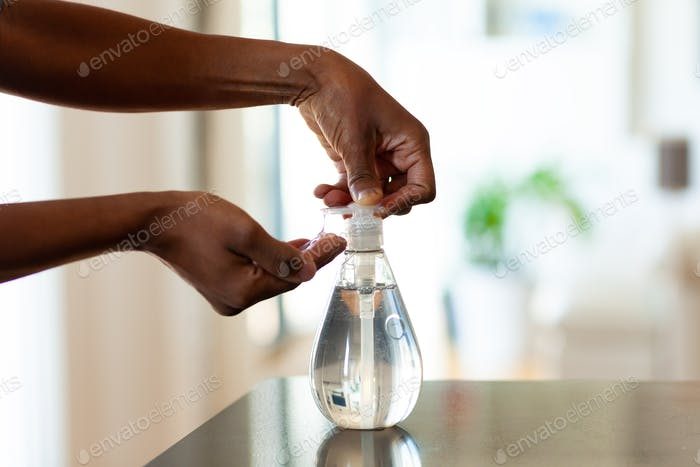 Black African American woman hand using antibacterial antiseptic hand sanitizer gel