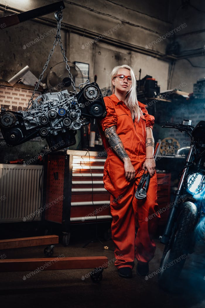 Blond female mechanic with tattooed hands in orange overalls stands in garage or workshop