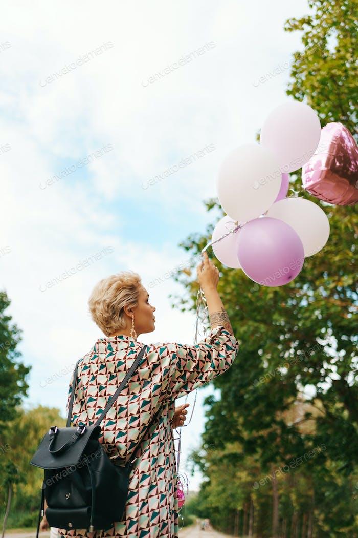 Mujer rubia con globos rosados