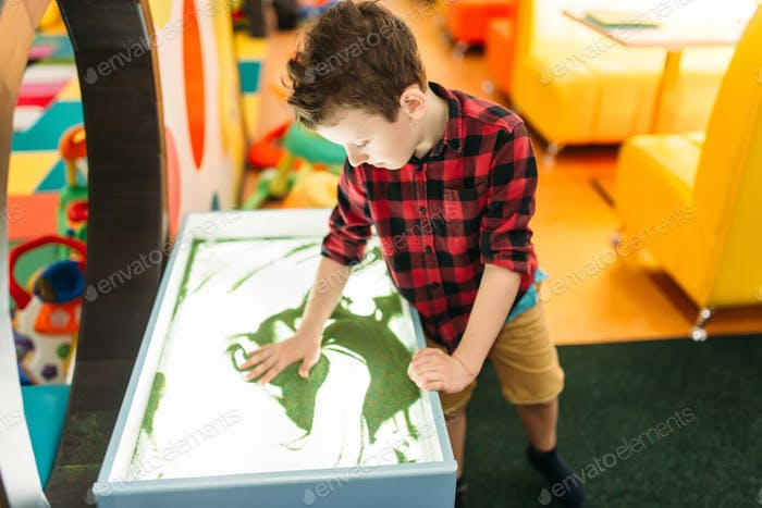 Young boy draws in the sand, entertainment center
