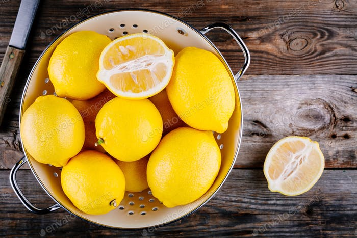 fresh organic lemons in a colander on a wooden background. Top view
