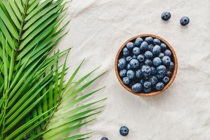 Blueberry in a wooden bowl on a linen napkin decorated with palm leaf.