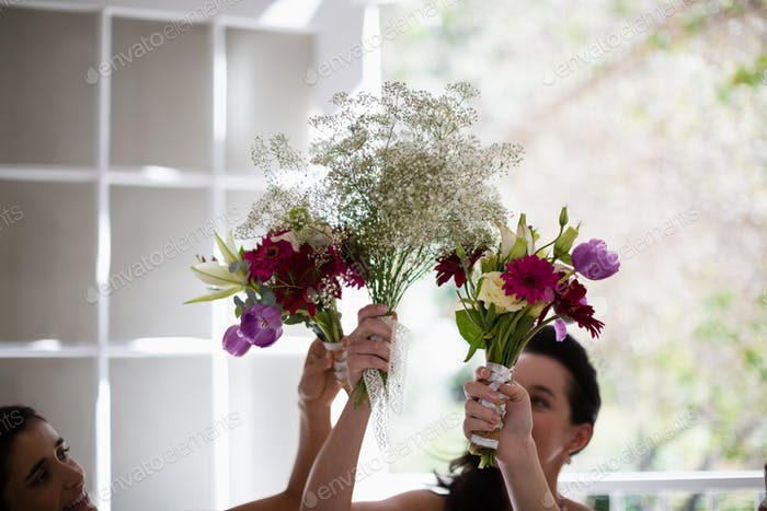 Bride and bridesmaids holding flower bouquet at home