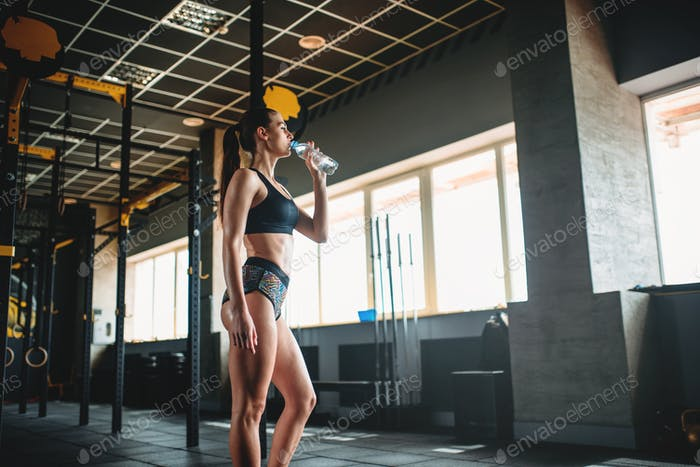 Female athlete drink water after training in gym