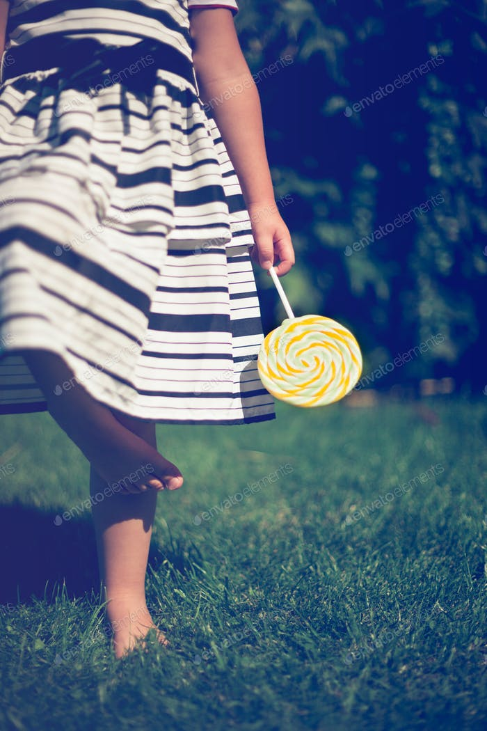Little girl holding a lollipop in her hand.