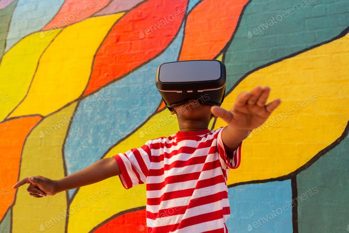 Cute playful African American schoolboy using virtual reality headset in the school playground