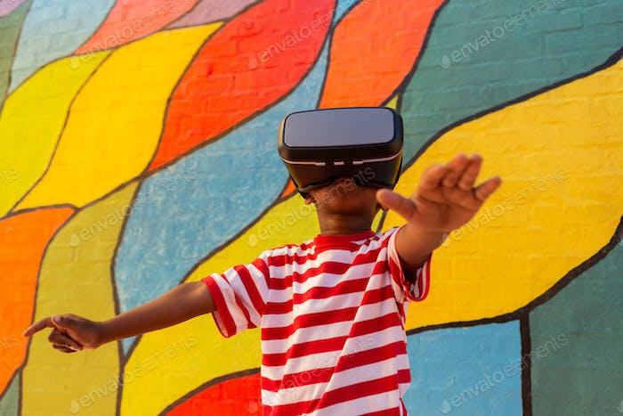 Niedlich verspielt African American Schuljunge mit Virtual Reality Headset in der Schule Spielplatz