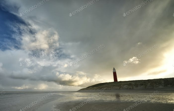 rainy cloud over red lighhouse on beach
