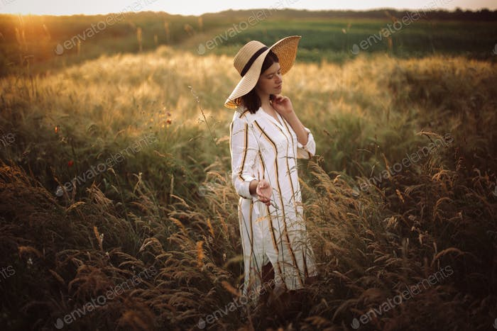 Woman in rustic dress and hat enjoying peaceful sunset in wildflowers and herbs in summer meadow