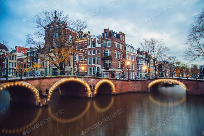 Amsterdam canals with bridge and typical Dutch houses.