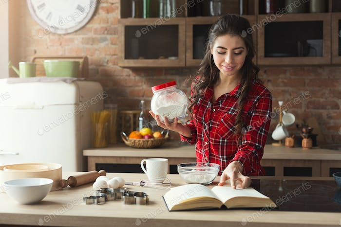 Happy young woman baking in loft kitchen