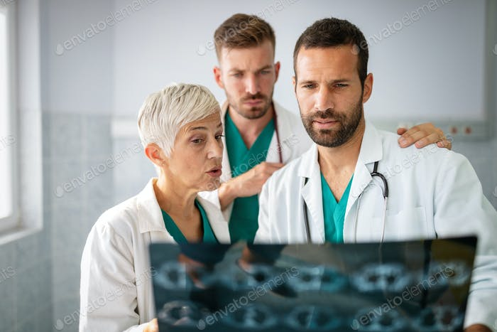 Medical team doctors checking on X-ray results in hospital