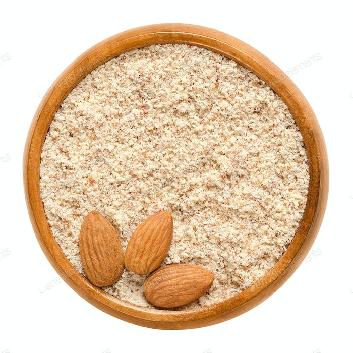 Shelled and ground almond nuts in wooden bowl over white
