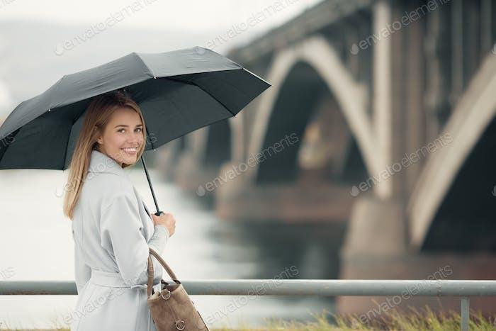 Junge Frau im blauen Mantel hält Regenschirm. Herbststadt