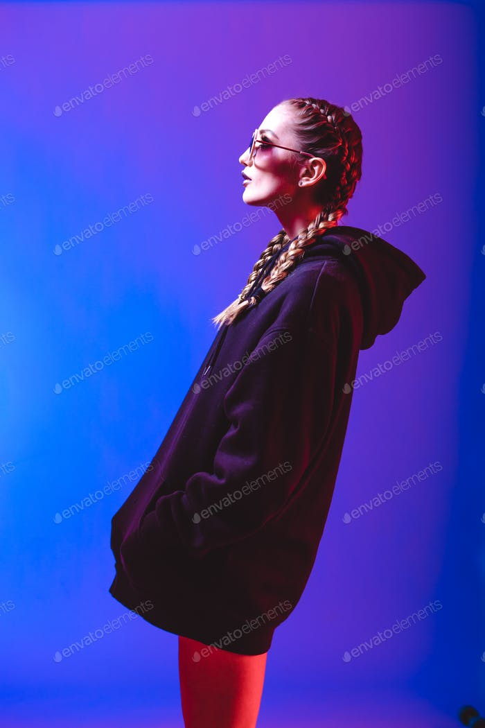 Portrait of fashion girl in a black sweater with a hood and sunglasses round shape in neon light in