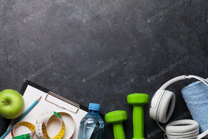 Fitnesskonzept Hanteln, Kopfhörer und Apfel