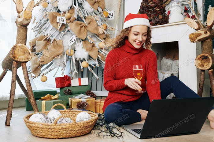 Woman sending e-mails with Christmas wishes