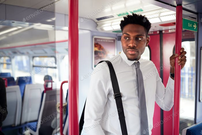 Businessman Standing In Train Commuting To Work
