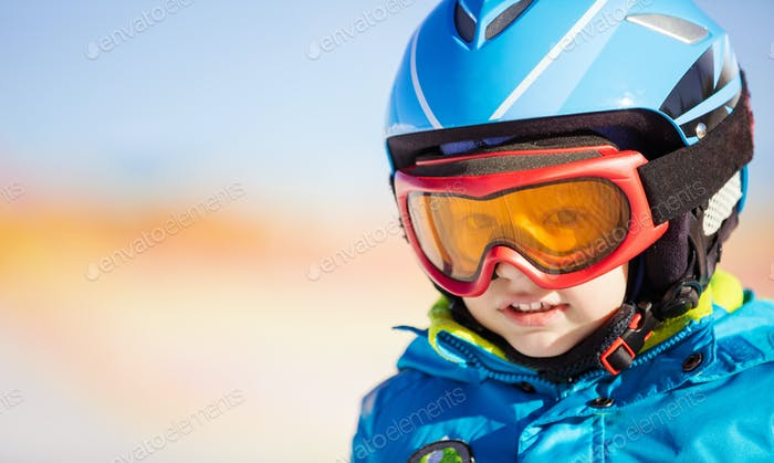 Little skier in safety helmet and goggles