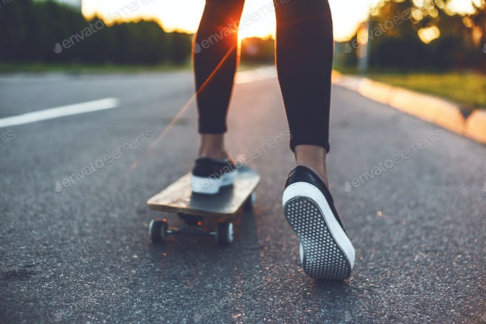 young skateboarder legs riding on skateboard