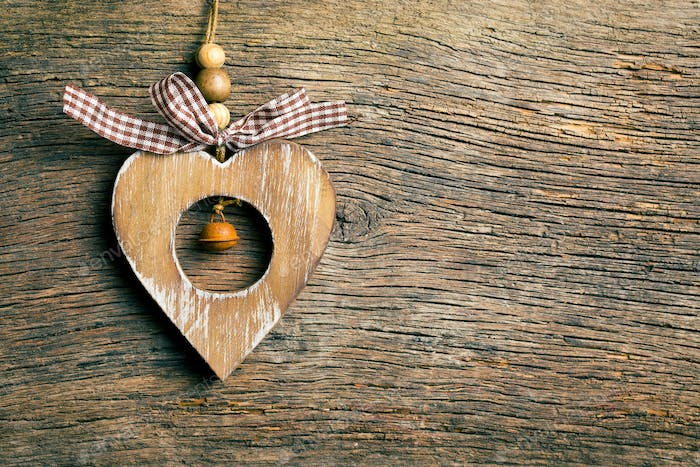 wooden heart hanging on wooden background