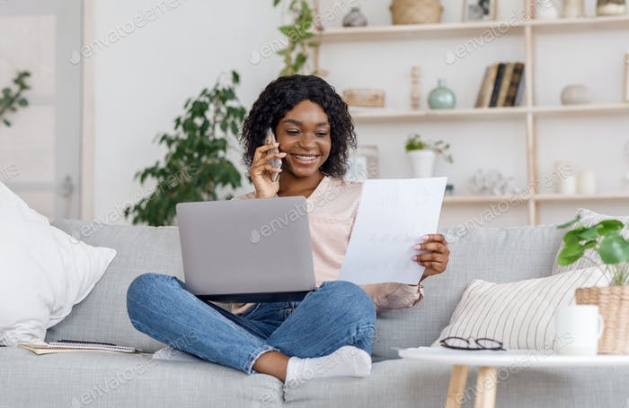 Black female entrepreneur working from home, discussing documents with client on cellphone
