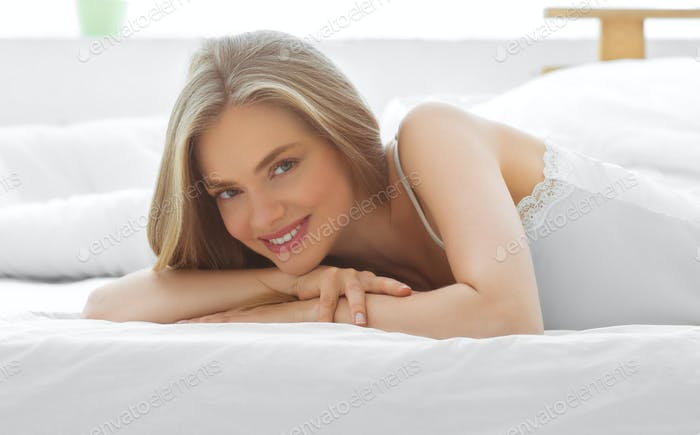 Beautiful woman home in bed relax happy smile blonde female beautiful model casual lifestyle