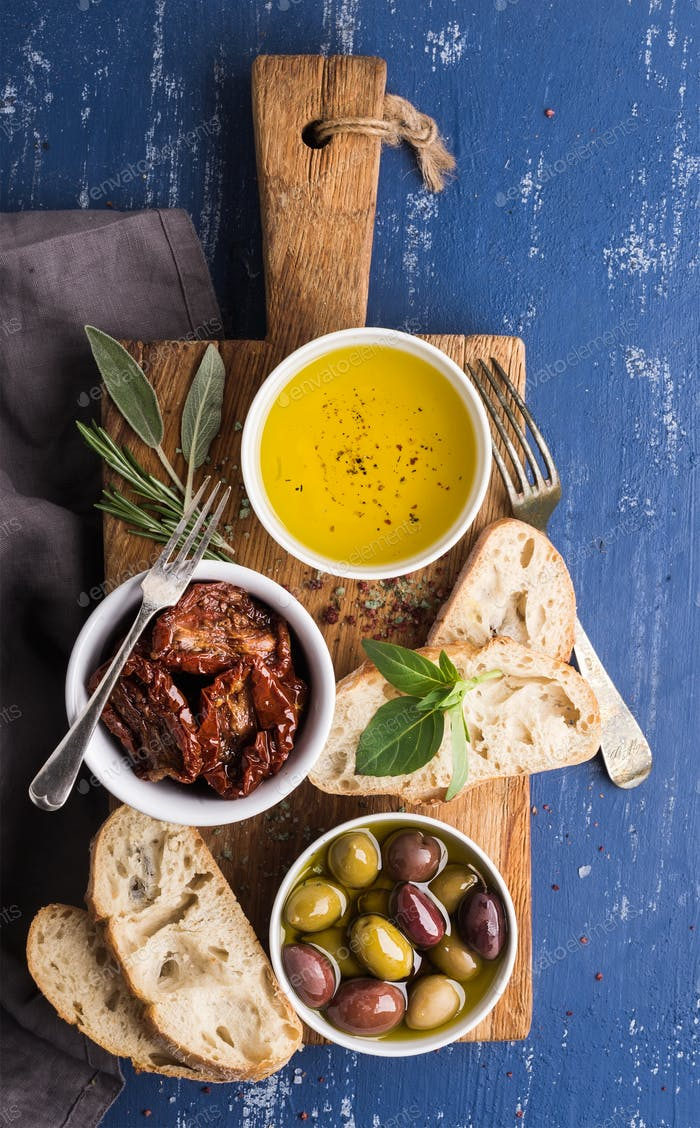 Mediterranean snacks set. Olives, oil, herbs and sliced ciabatta bread