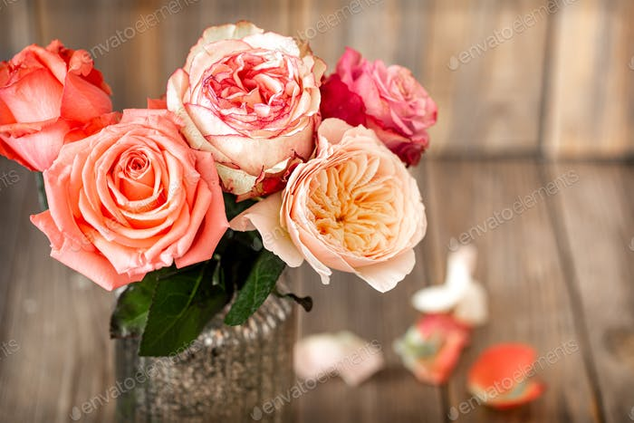 Beautiful roses in a vase on a wooden background