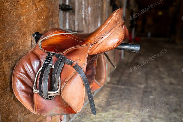 Brown shabby leather saddle with black bridles hanging on steel bar
