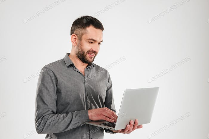 Concentrated businessman using laptop computer.