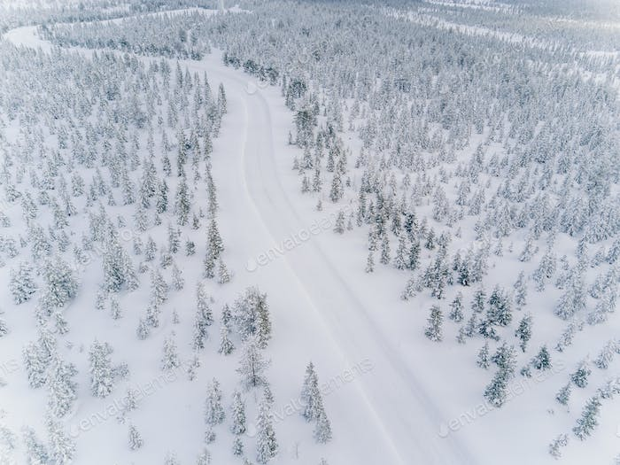 Aerial drone view of road in idyllic winter landscape.