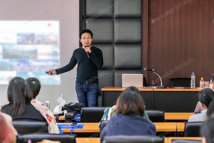 Asian Speaker or lecture with casual suit on the stage presenting via projector screen