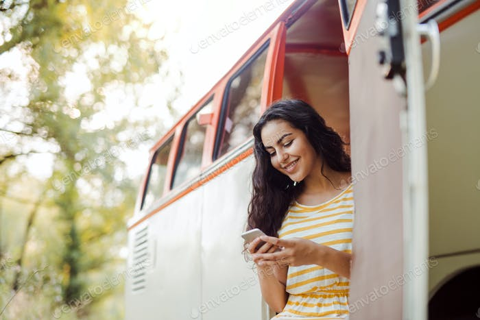 A young girl with smartphone by a car on a roadtrip through countryside, texting.