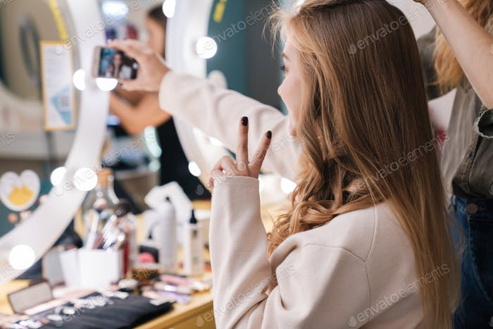 Optimistic young beautiful woman client take a selfie