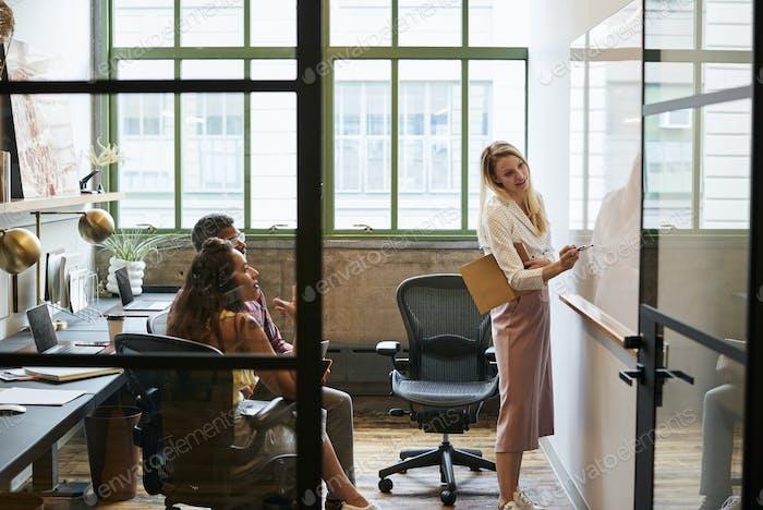Frau beim Whiteboard im Teammeeting, durch offene Tür gesehen